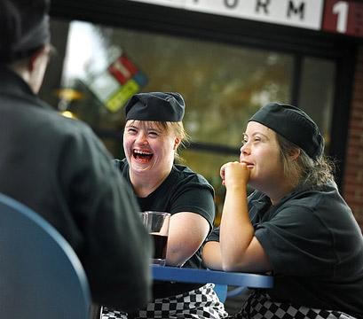 Tre camerieri scherzano seduti intorno ad un tavolino, davanti ad una bibita, in una stazione. Kate, una di loro, ha la sindrome di Down. © Richard Bailey