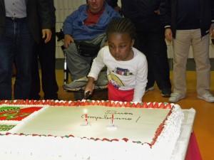 Bambina taglia la torta per il compleanno della UILDM