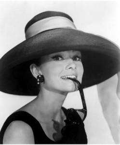 Un bel primo piano di Audrey Hepburn con un bel cappello e degli orecchini mentre tiene in bocca la stecca di un paio di occhiali.