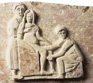 Rilievo in terracotta raffigurante una scena di parto, tomba di Scribonia Attice e M. Ulpio Amerimno, necropoli del'Isola Sacra, Ostia, 140 d.C. – Ostia, Museo Ostiense. La raffigurazione riportata sulla tomba indica che la donna sepolta era un'ostetrica.