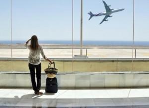 Una donna con bagaglio a mano attende di prendere l'aereo. La donna è fotografata in piedi, di spalle mentre osserva, attraverso una vetrata, un aereo appena decollato.