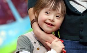 Una bambina con sindrome di Down stringe la mano smaltata di una donna che l'accosta a sé.