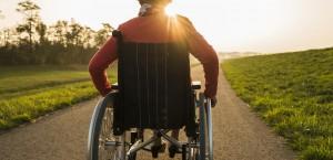 Una donna con disabilità, ritratta di spalle, e con il sole sullo sfondo, si incammina lungo un sentiero.