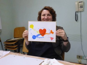 Un'immagine in cui Renata Sorba mostra un disegno con al centro un cuore rosso, ed intorno altri elementi colorati, poiché Renata, pur essendo cieca, ama i colori vivaci.